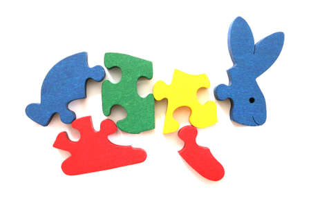 Colorful wooden rabbit puzzle toy partically scattered on white background