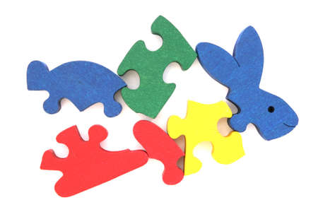 Colorful wooden rabbit puzzle toy partially scattered on white background photo