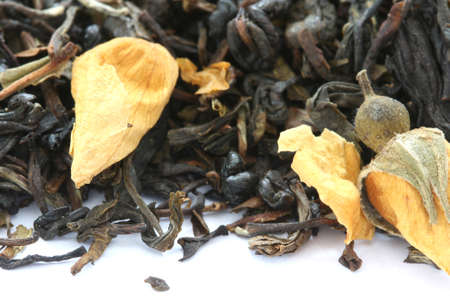 flavoured: Dry black tea flavored with dry flower buds on white background
