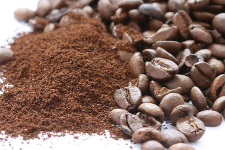 noone: Whole and ground coffee beans scattered on white background