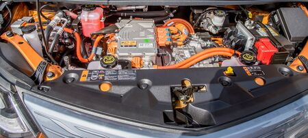 under the hood of an orange electric car, technology of the future