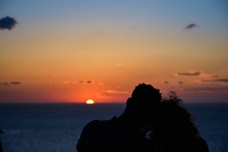 Silhouette of a loving couple on the background of the setting sun, islands and sea. Santorini. Greece. Just married. Walk at sunset. Romantic scene.