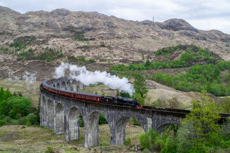 Glenfinnan Viaduct, Scotland. Travel/tourist destination in Europe. Old historical steam train riding on film scene famous viaduct bridge. Highlands, mountains, outdoor background.