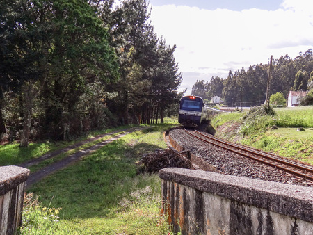 The Transcantabrico luxury tourist train leaving a curve to face a bridge