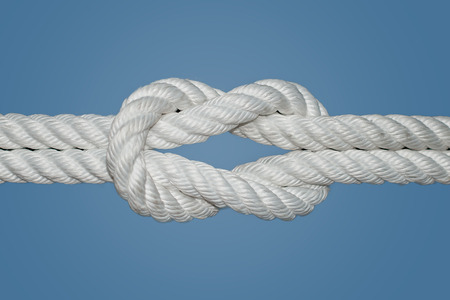 The Reef Knot or Square Knot is quick and easy to tie; it is a good knot for securing non-critical items  This knot was used for centuries by sailors for reefing sails, hence the name Reef Knot  Stock Photo