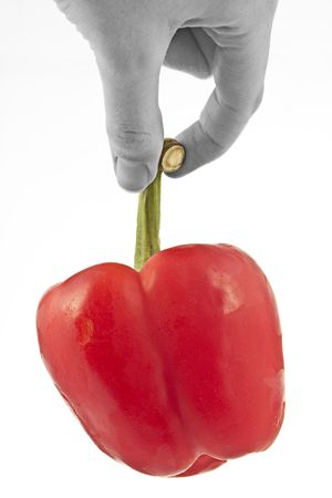 hand held: Una mano detenuti pepe rosso, colore spuntato  Archivio Fotografico