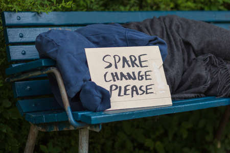 Homeless man on a park bench with a carboard sign Stock Photo