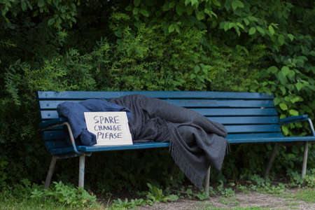 destitute: Homeless man on a park bench with a carboard sign Stock Photo