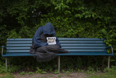 scourge: Homeless man on a park bench with a cardboard sign Stock Photo