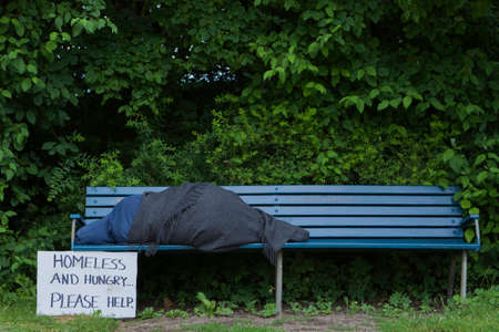 Homeless man on a park bench with a cardboard sign Stockfoto