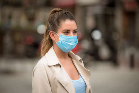 girl with medical mask walks down the street during the coronavirus quarantine