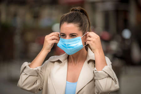 girl puts on a medical mask on the street during the coronavirus quarantine