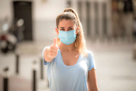 girl makes positive gesture with medicinal mask during coronavirus quarantine