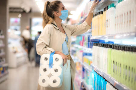 girl in the supermarket with toilet paper during the coronavirus quarantine
