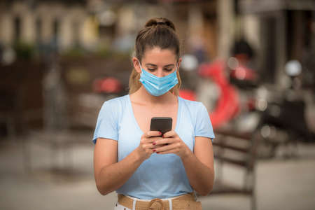 girl uses a phone in the street with a medical mask during the coronavirus quarantine 版權商用圖片