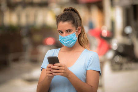girl uses a phone in the street with a medical mask during the coronavirus quarantine