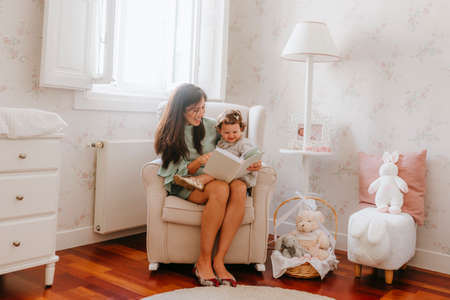 little girl having fun sitting on her pregnant mother in the room