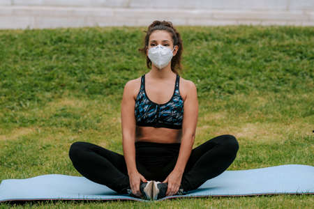 Runner wearing medical mask, Coronavirus pandemic Covid-19. Sport, Active life in quarantine surgical sterilizing face mask protection. Outdoor run on athletics track in Corona Outbreak. yoga park
