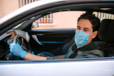 a man driving a car puts on a medical mask during an epidemic, a taxi driver in a mask, protection from the virus. Driver in white car. coronavirus, disease, infection, quarantine, covid-19 Foto de archivo