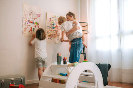 young mother with her two children painting at home. entertainment during quarantine. family at home. coronavirus.