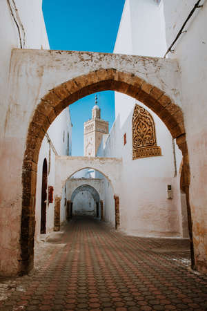 typical street in the medina of Casablanca in Morocco. Mosque background. Colorful street