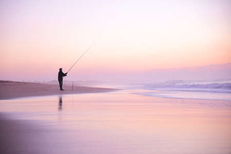 Silhouette of a fisherman fighting fish with a long fishing rod on ocean beach in front of beautiful sunset with orange and pink clouds