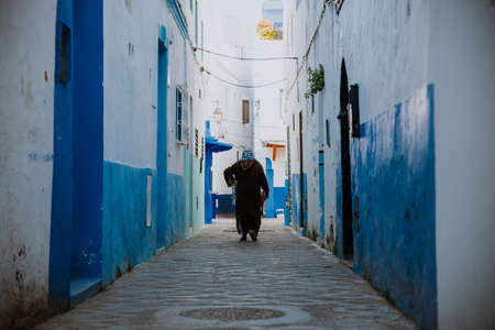Asilah, Morocco - 19 September 2019: A narrow street in with blue & white & red style.