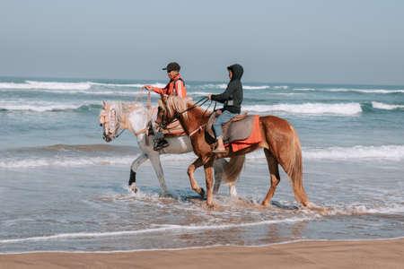 Horse Ride in front of the Sea in full Sunset, Moroccan coast, Casablanca, Morocco Foto de archivo