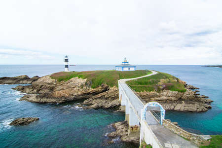 The Illa Pancha Lighthouse is located on a small island connected to land by a bridge. Light the port and estuary of Ribadeo. The sea hits the rocks arround. Isla Pancha, Ribadeo, Lugo, Galicia, Spain Foto de archivo
