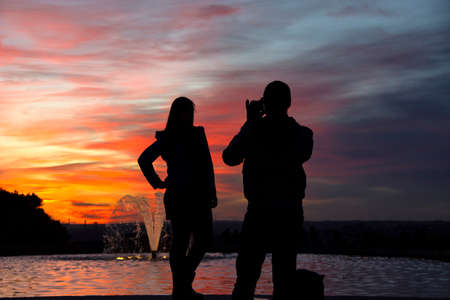 silhouette of a man holding a cellphone taking pictures outside during sunrise or sunset. Madrid.