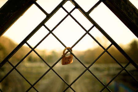 backlight of a closed padlock on a fence in a sunset