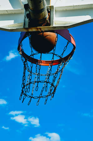 A basketball hoop with a basketball. The basketball is going in the hoop. The hoop has a double rim and a chain net. Its shot from below with the sky as a background. Stock Photo