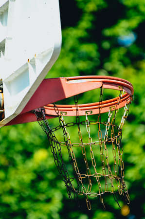 A basketball hoop showing only the top part. Its a double rim and a chain net. Its shot from the side with trees as a background.