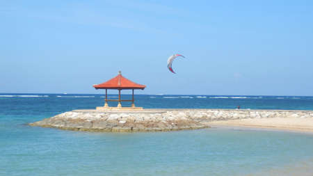 Kite surfing in the waves along Sanur beach with a traditional gazebo out in the ocean, Bali