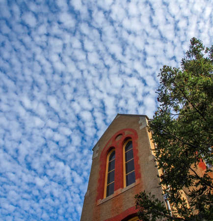stratus: Old Building with blue sky and interesting patterns in the clouds Stock Photo