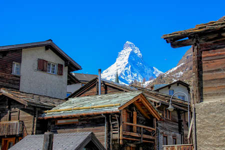 bathed: Old wooden lodges in Zermatt with a sun bathed Matterhorn behind. Stock Photo