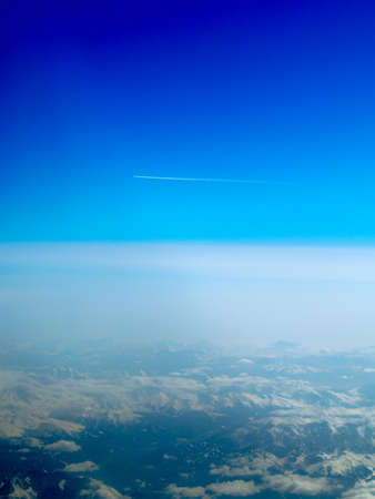 vapour: Aeroplane flying through clear blue sky over the Swiss Alps with vapour trail