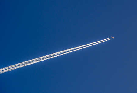aircraft aeroplane: Aeroplane flying through clear blue sky with vapour trails Stock Photo