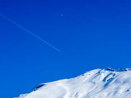 vapour: Aeroplane flying above a mountain with vapour trails and para-sailer Stock Photo