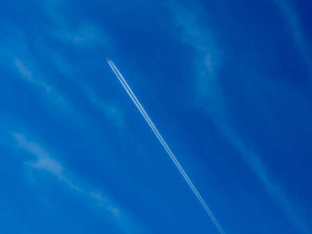 vapour: Aeroplane flying through clear blue sky with vapour trails Stock Photo