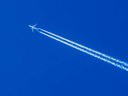 vapour: Airplane flying through clear blue sky with vapor trails