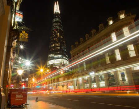 Central London city street at night with the Shard.