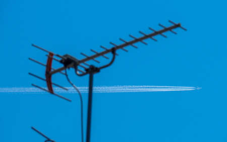 Airplane with vapor trails flying through blue sky with TV antenna in foreground.