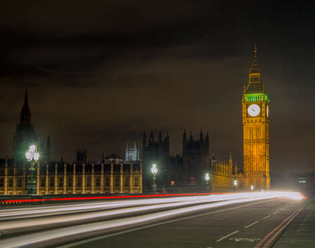 Big Ben and Houses of parliament at night with traffic rushing pass