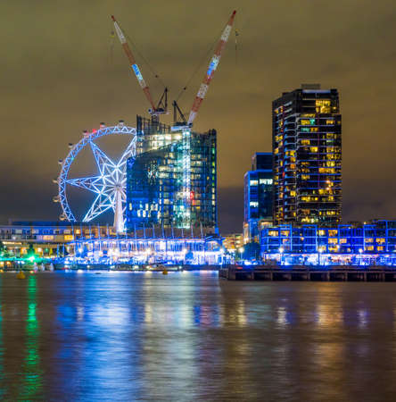 Melbourne Docklands at night with building construction and  observation wheel