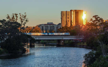 Train crossing the Yarra River with sun reflecting of a building, melbourne.