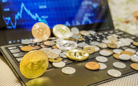 Bitcoin and currency coins scattered on computer keyboard with exchange charts of crypto currency on the laptop screen.