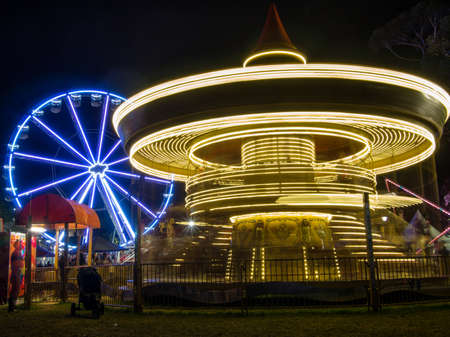 AUSTRALIA, MELBOURNE - March 08, 2015: Bright illuminated lights from festival merry go round and ferris wheel