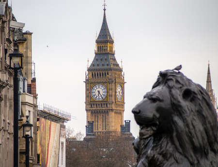 Trafalgar Square lion statue with Big Ben in the background, London