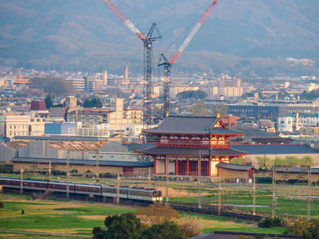 JAPAN, NARA - APRIL 12, 2017: Train passing in front of Suzaku Gate of Heijo Palace in Nara withtall cranes behind
